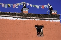 Nepal, Mustang, Young monks waving out a window of monastery. - Jill Gocher