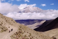 Nepal, Mustang, Tourists walking along high path, surrounded by mountains. - Jill Gocher