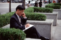 Man in business suit, using mobile phone and writing on note pad - Alex Microstock02