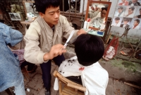 Vietnam, Hanoi, Barber cutting hair - Alex Mares-Manton