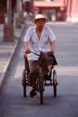 China, Beijing, man cycling, hat on head - Alex Mares-Manton