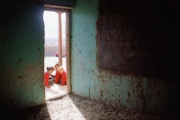 India, Ladakh, School girls sitting in front of doorway of classroom. - Mary Grace Long