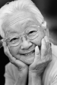 Mature woman with glasses, with hands on head, smiling. - Mary Grace Long