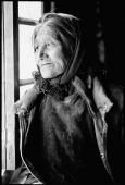 India, Ladakh, Small village near Leh, Elderly lady looking out of window. - Mary Grace Long