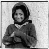 India, Ladakh, Portrait of young girl arms crossed, smiling. - Mary Grace Long