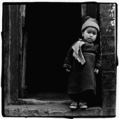 India, Ladakh, Portrait of little boy standing in doorway. - Mary Grace Long