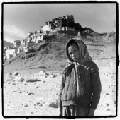 India, Ladakh, Portrait of young girl, monastery at background. - Mary Grace Long