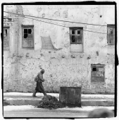 India, Ladakh, Leh, man walking past building. - Mary Grace Long