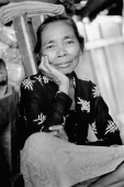 Indonesia, Java, Portrait of lady resting head on hand, smiling. - Mary Grace Long