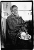 India, Dharamsala, Indian girl on bus holding Hindu icons. - Mary Grace Long