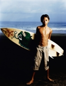 Indonesia, Bali, Kuta Beach, Young surfer holding surfboard on the beach. - Martin Westlake