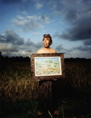 Indonesia, Bali, Ubud, Balinese artist holding painting in rice field. - Martin Westlake