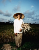 Indonesia, Bali, Ubud, Balinese woman holding rice stalks at harvest time. - Martin Westlake