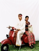 Indonesia, Bali, Ubud, Balinese wedding couple in ceremonial dress, sitting on motor scooter, woman carrying offering. - Martin Westlake