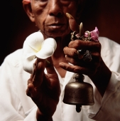Indonesia, Bali, Ubud, Hindu priest holding prayer bell and Frangipani flower. - Martin Westlake