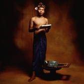 Indonesia, Bali, Ubud, Young Balinese man with his paintings of Bali scenery. - Martin Westlake