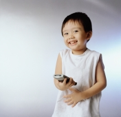 Boy, 3 years old holding remote control, smiling. - Erik Soh