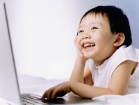 Boy, 3 years old, using laptop, smiling. - Erik Soh