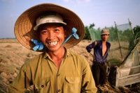 Vietnam, Mekong Delta, Smiling farm workers threshing rice. (grainy) - Martin Westlake