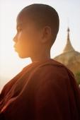 Myanmar (Burma), Bago, Kyaityo, Novice monk in front of hanging rock pagoda, profile. (grainy) - Martin Westlake