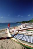 Indonesia, Bali, Sanur Beach, Fishing boats (Jukung) lined up on beach. (grainy) - Martin Westlake