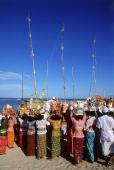 Indonesia, Bali, Tanjung Benoa, Women carrying offerings at Melasti ceremony on beach. (grainy) - Martin Westlake