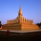 Laos, Vientiane, Buddhist monk walks past Pha That Luang Temple. (grainy) - Martin Westlake