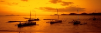 Indonesia, Flores, Labuanbajo, Sunset across beach, fishing boats in foreground. (grainy) - Martin Westlake