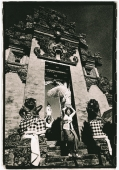 Indonesia, Bali, Gianyar, Women with offerings passing through temple gates. (artistic grain) - Martin Westlake