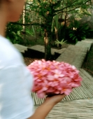 Philippines, Boracay, Mandala Spa, Spa girl carries flowers to massage pavilion. - Martin Westlake