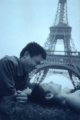 Young couple lying on grass, Eiffel Tower in background. - Leila  Pivetta