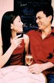 Young couple sitting at outdoor cafe holding wine glasses, smiling. (high-grained) - Leila  Pivetta