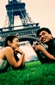 Young couple lying on grass, holding camera, Eiffel Tower in background. (high-grained) - Leila  Pivetta