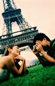 Young couple lying on grass, young woman posing for camera, smiling, Eiffel Tower in background. (high-grained) - Leila  Pivetta