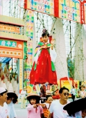 China, Hong Kong, Cheung Chau Island, girl wearing a traditional costume, standing on tiny foothold held up by another girl during the Bun Festival procession in 2000 - Carsten Schael