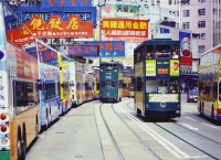 China, Hong Kong, Buses along King's Road, at Olympic Theatre, trams are passing by - Carsten Schael
