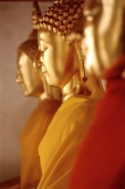 Buddha statues in a row, sideview - Alex Mares-Manton