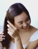 Teenage girl combing hair, smiling. - Erik Soh