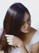 Teenage girl combing hair. - Erik Soh