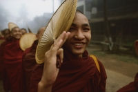 Myanmar (Burma), Bago, Buddhist monk holding a fan, in line to collect alms. - Martin Westlake