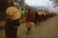 Myanmar (Burma), Bago, Buddhist monks holding fans line up to collect alms. - Martin Westlake