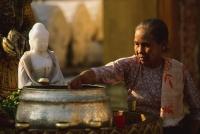 Myanmar (Burma), Yangon, Shwedagon Paya, Worshipper at Washing Buddha image at planetary post. - Martin Westlake