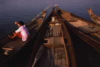 Myanmar (Burma), Pyay, Woman waiting on canoe on the Irrawaddy river. - Martin Westlake