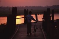 Myanmar (Burma), Mandalay, Man with bicycle crossing the U Bein bridge at sunset. - Martin Westlake