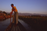 Myanmar (Burma), Inle lake, Boatman dressed in longyi steering canoe down backwaters. - Martin Westlake