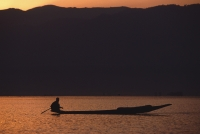 Myanmar (Burma), Inle lake, Silhouette of fisherman in canoe at sunrise. - Martin Westlake