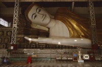 Myanmar (Burma), Bago, Shwethalyaung, Buddhist monk prays in front of reclining Buddha. - Martin Westlake