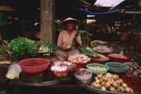 Vietnam, Ben Thanh market, Ho Chi Minh city, Woman selling fruit and vegetables at market stall. - Martin Westlake