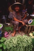 Vietnam, Cai Be, Mekong Delta, Woman selling vegetables at market stall. - Martin Westlake