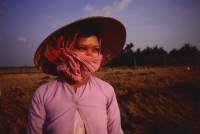 Vietnam, Outside Vinh Long, Mekong delta, Rice farmer at rice harvest/threshing time. - Martin Westlake